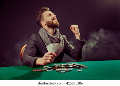Successful poker player enjoying his win at poker table with chips and cards