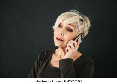 A successful positive elderly female consultant is negotiating a cell phone. Communication between people using modern technology.