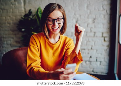 Successful positive young woman with short haircut watching live stream online on smartphone and celebrating victory of favourite team.Emotional hipster girl happy with win in online contest