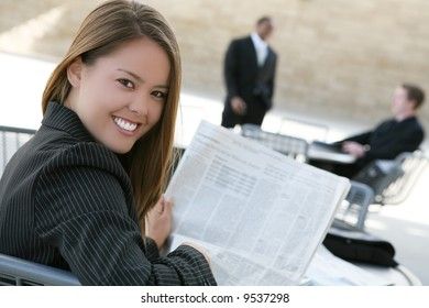 A successful, pretty business woman reading the newspaper