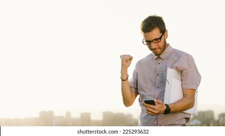 Successful professional casual man gesturing and checking cellphone messages towards city skyline. Entrepreneur enjoys success in job.