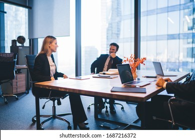 Successful professional experts in elegant wear discussing productive plan for work of employees during business meeting in conference room, concept of corporate brainstorming and collaboration