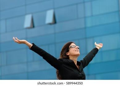 Successful professional woman raising arms. Happy businesswoman celebrating job goals success outside.