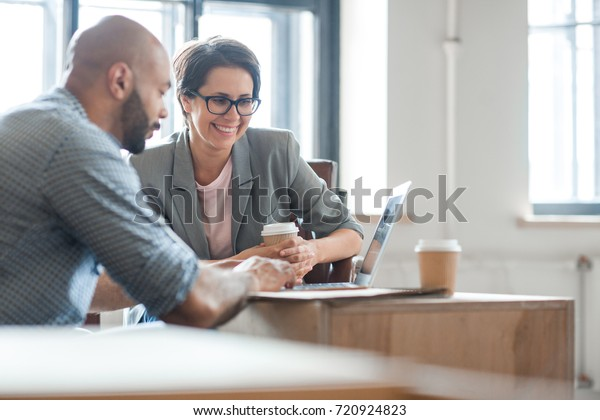 Successful professionals looking through online ideas for their business project