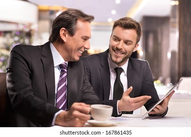 Successful project. Two cheerful business people in formalwear discussing something and smiling while one of them pointing digital tablet