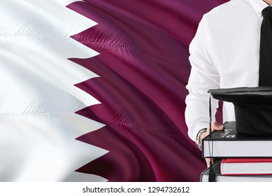 Successful Qatari student education concept. Holding books and graduation cap over Qatar flag background.