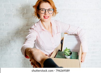 Successful red hair business lady with box in glasses shaking male hand, hr manager welcoming job applicant, female executive getting acquainted with new manager, nice to meet you.