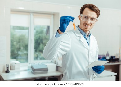 Successful results. Delighted nice man looking at the test tube while conducting a successful research