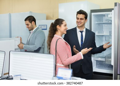 Successful  seller and happy couple at household appliances section of supermarket