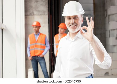 Successful senior architect is showing okay sign. He is pleased with building. The man is smiling. Handsome young workers are standing and resting behind him