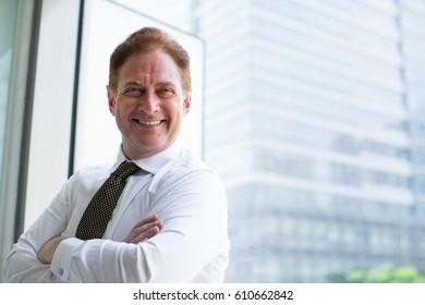 Successful senior businessman standing at window