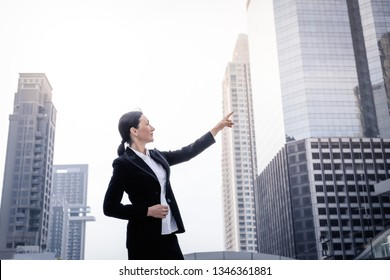 Successful senior businesswoman leader pointing and looking forward over modern building background