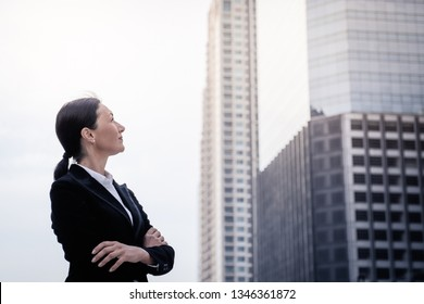 Successful senior businesswoman leader standing and looking forward over modern building background