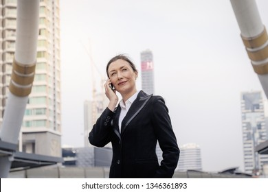 Successful senior businesswoman leader talking on mobile phone with modern building background