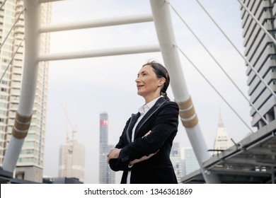 Successful senior caucasian businesswoman leader standing over modern building background
