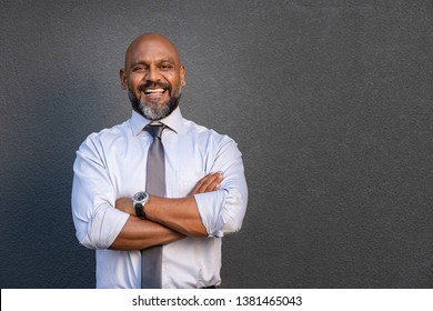 Successful senior man with folded arms standing over grey background. Mature black businessman in shirt and tie looking at camera. Portrait of joyful business man on a grey wall with copy space.