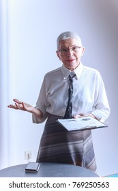 Successful senior old woman holding a graphic chart, giving a lecture or an explanation