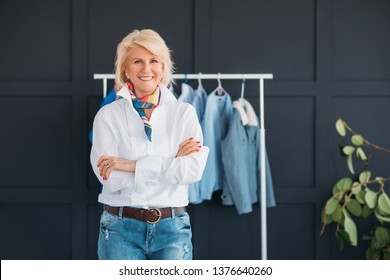 Successful senior woman. Fashion boutique business. Smiling aged lady at showroom workspace. Elegance and confidence.