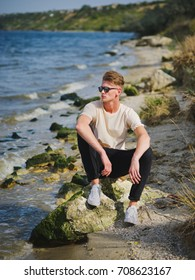 A successful, serious guy in cool dark sunglasses sitting and relaxing near the blue water on a blurred natural background. A male teen enjoying vacation trip near the sea. Copy space.