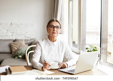 Successful serious senior 60 year old female personal coach writing down important information in notebook, working at home office with open laptop, mug and books on desk, consulting people online