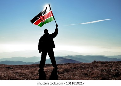 Successful silhouette man winner waving Kenya flag on top of the mountain peak