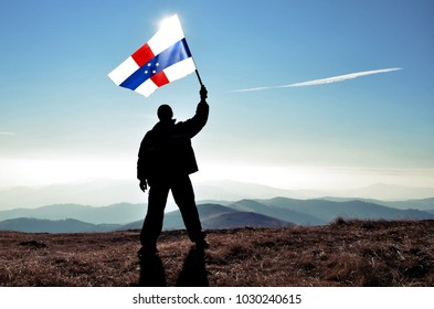 Successful silhouette man winner waving Netherlands Antillesflag on top of the mountain peak