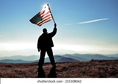 successful silhouette man winner waving American flag on top of the mountain peak