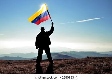 successful silhouette man winner waving Venezuela flag on top of the mountain peak