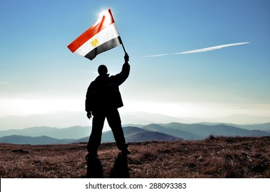 successful silhouette man winner waving Egypt flag on top of the mountain peak