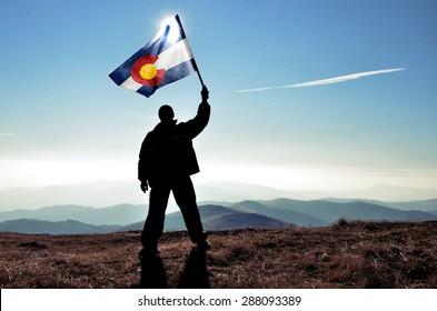 successful silhouette man winner waving Colorado flag on top of the mountain peak