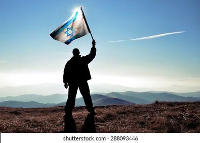 successful silhouette man winner waving Israel flag on top of the mountain peak