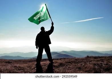 successful silhouette man winner waving Saudi Arabia flag on top of the mountain peak