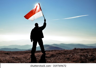 successful silhouette man winner waving Indonesia flag on top of the mountain peak