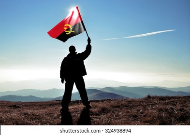 successful silhouette man winner waving Angola flag on top of the mountain peak