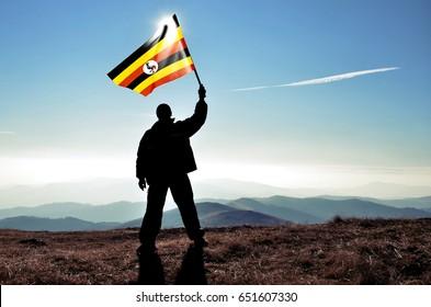 Successful silhouette man winner waving Uganda flag on top of the mountain peak