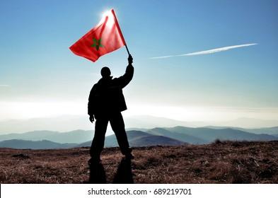 Successful silhouette man winner waving Morocco flag on top of the mountain peak