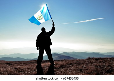 Successful silhouette man winner waving Guatemala flag on top of the mountain peak
