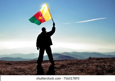 Successful silhouette man winner waving Cameroon flag on top of the mountain peak