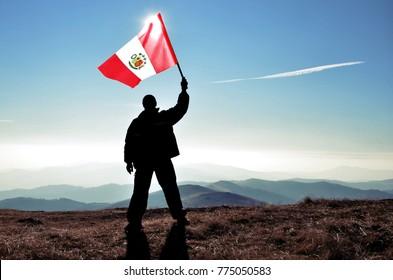 Successful silhouette man winner waving Peru flag on top of the mountain peak