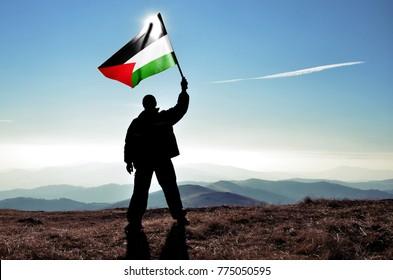 Successful silhouette man winner waving Palestine flag on top of the mountain peak