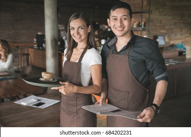 Successful small business owner or waitress proudly standing in front of their cafe or coffee shop