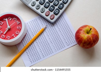 Successful and smart education concept: There are red apple, clock, calculator, answers sheet and yellow pencil isolated on white background. Exam or test period.