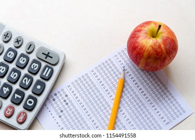 Successful and smart education concept: There are red apple, calculator, answers sheet and yellow pencil isolated on white background. Exam or test period.