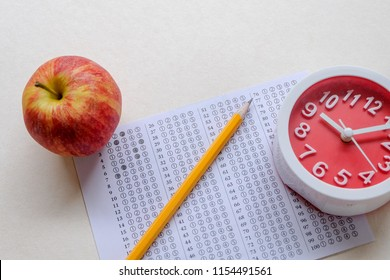 Successful and smart education concept: There are red apple, clock, answers sheet and yellow pencil isolated on white background. Exam or test period.