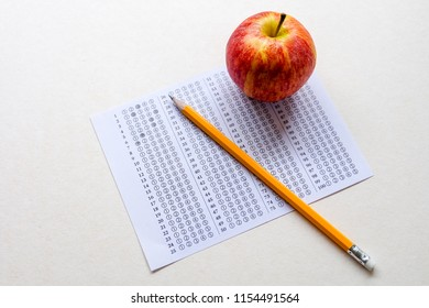 Successful and smart education concept: There are red apple, answers sheet and yellow pencil isolated on white background. Exam or test period.