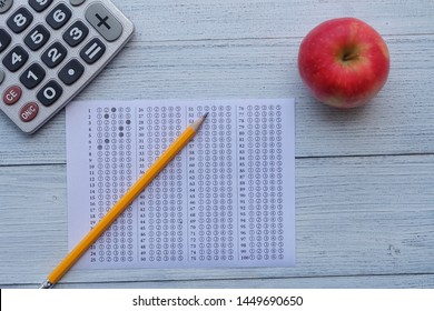 Successful and smart education concept: There are red apple,calculator, answers sheet and yellow pencil isolated on wooden desk background. Exam or test period.