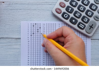 Successful and smart education concept: There are hand with yellow pencil,calculator and answers sheet on wooden desk background. Exam or test period.