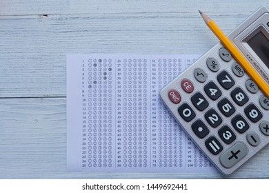 Successful and smart education concept: There are calculator, answers sheet and yellow pencil  on wooden desk background. Exam or test period.