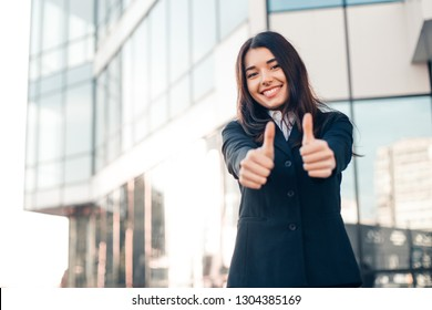 Successful smile businesswoman or entrepreneur shows thumbs up standing in front of his office.