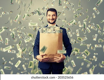 successful and smiley businessman holding paper bag with money under dollar's rain